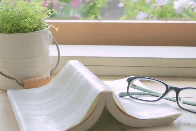 窓際の本と眼鏡の画像